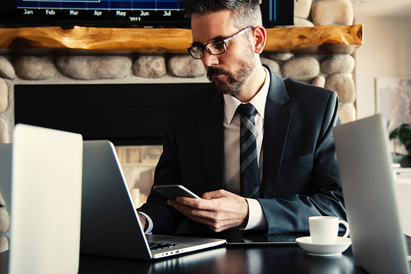 man dressed in suit sitting in front of a laptop while holding a cell phone