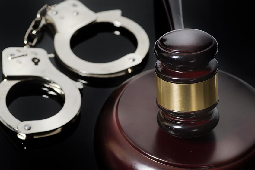 silver handcuffs and a gavel